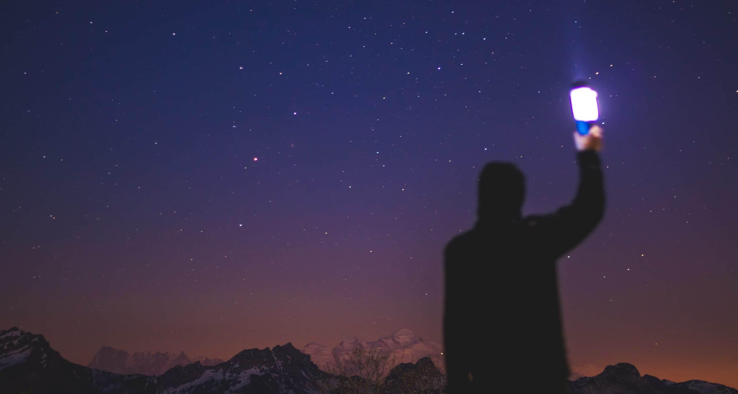 Silhueta de pessoa observando céu noturno estrelado.