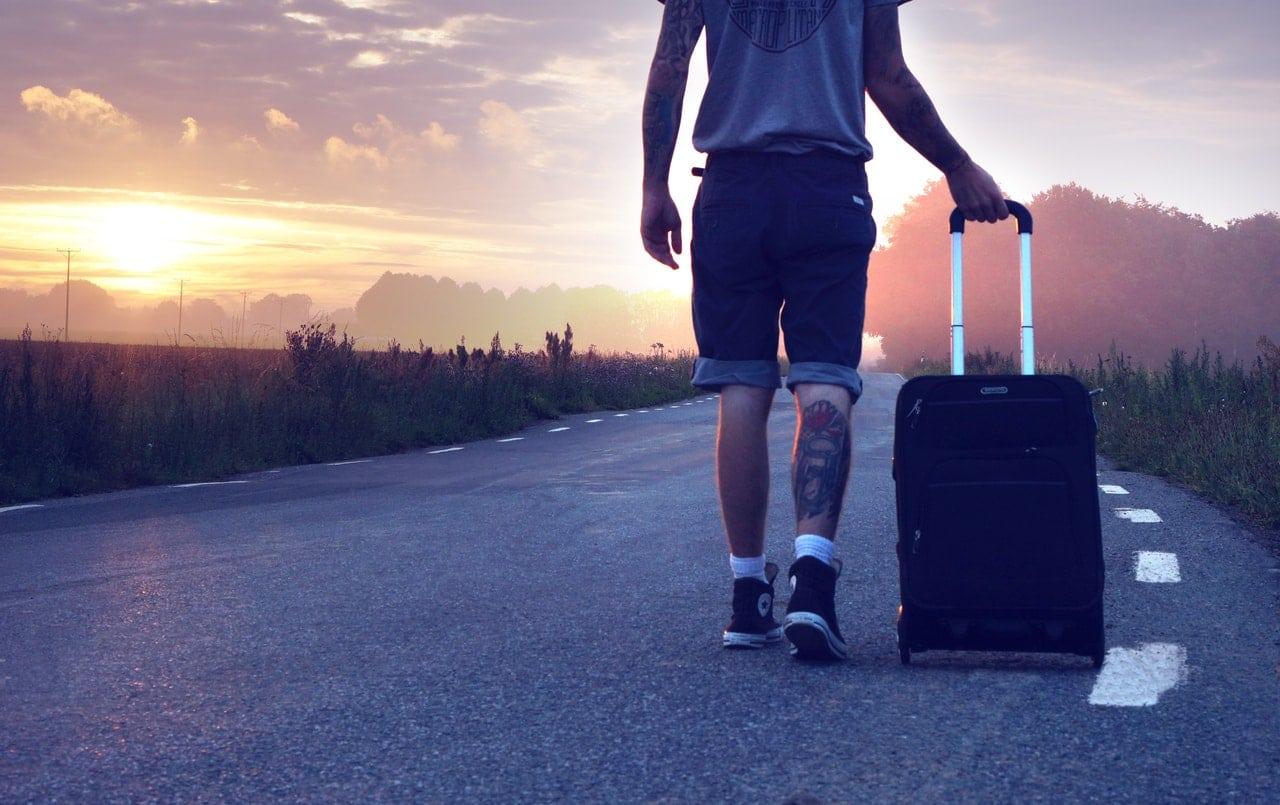 Homem pela metade andando com mala