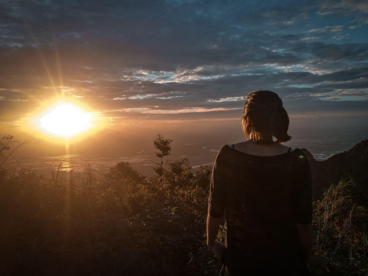 Mulher de costas olhando sol