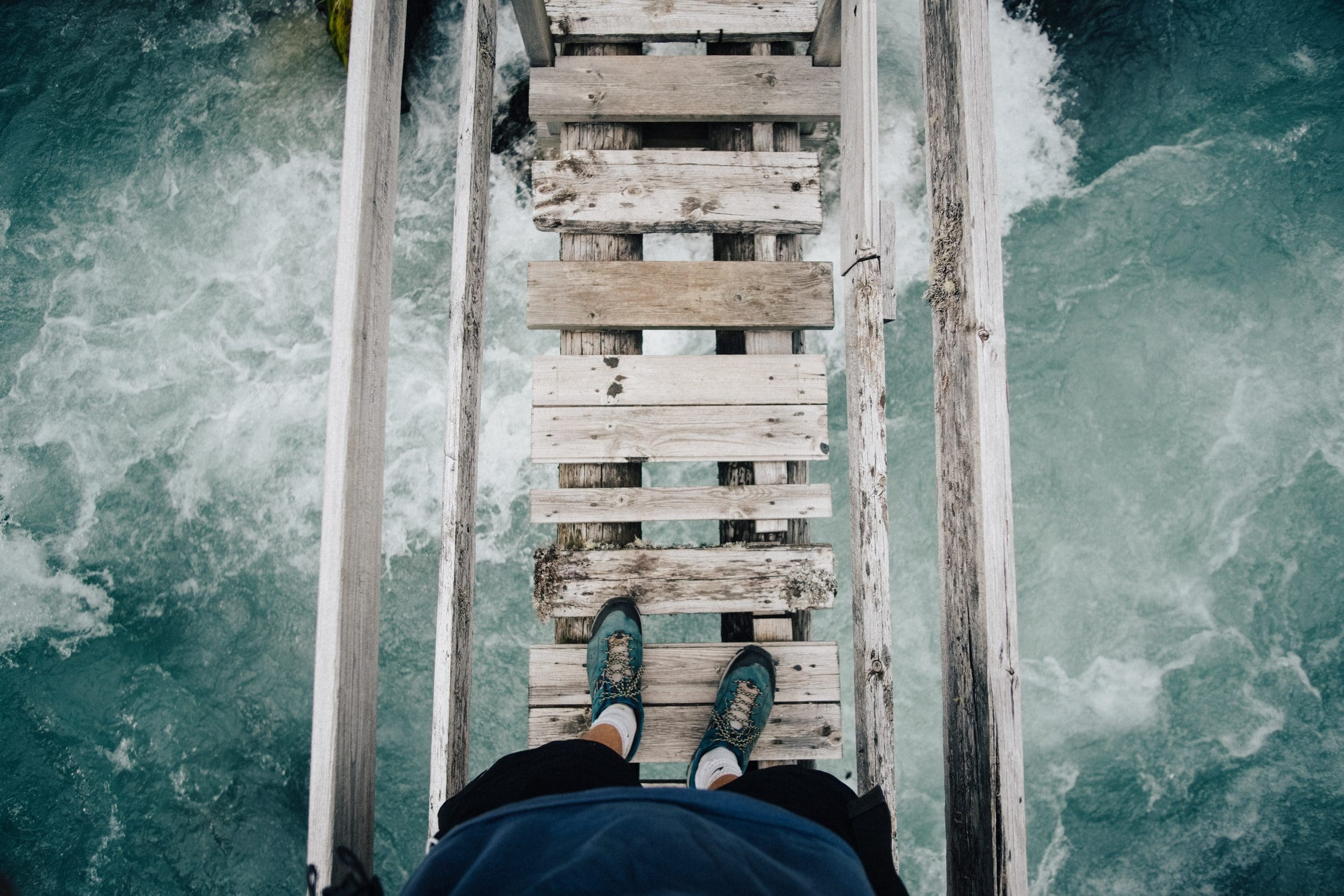 Pés em ponte de madeira com mar ao fundo