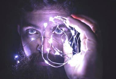 Homem segurando luzes no rosto