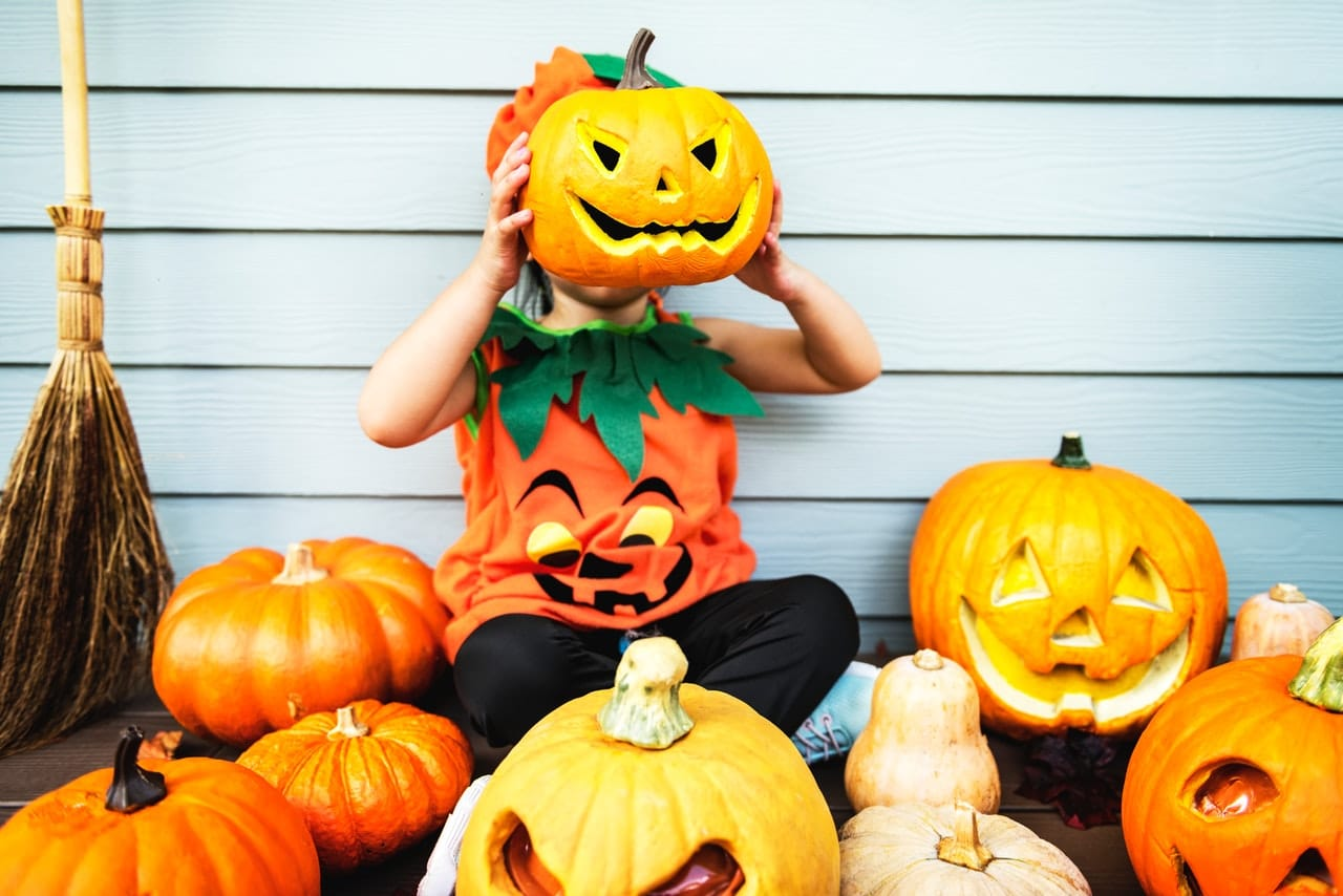 Criança segurando abóbora de halloween