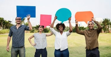 Pessoas diferentes segurando balões de fala coloridos