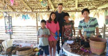 Colunista posando com povos indígenas dentro de uma cabana.