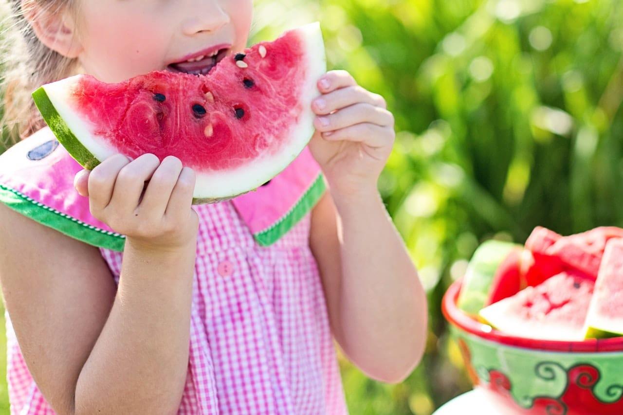 Criança mordendo melancia