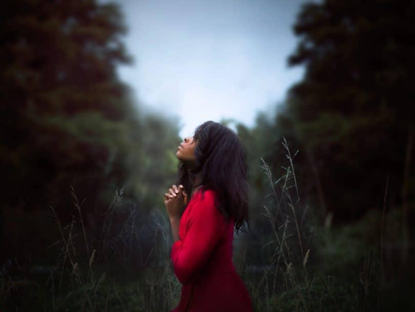 Mulher rezando olhando para o céu