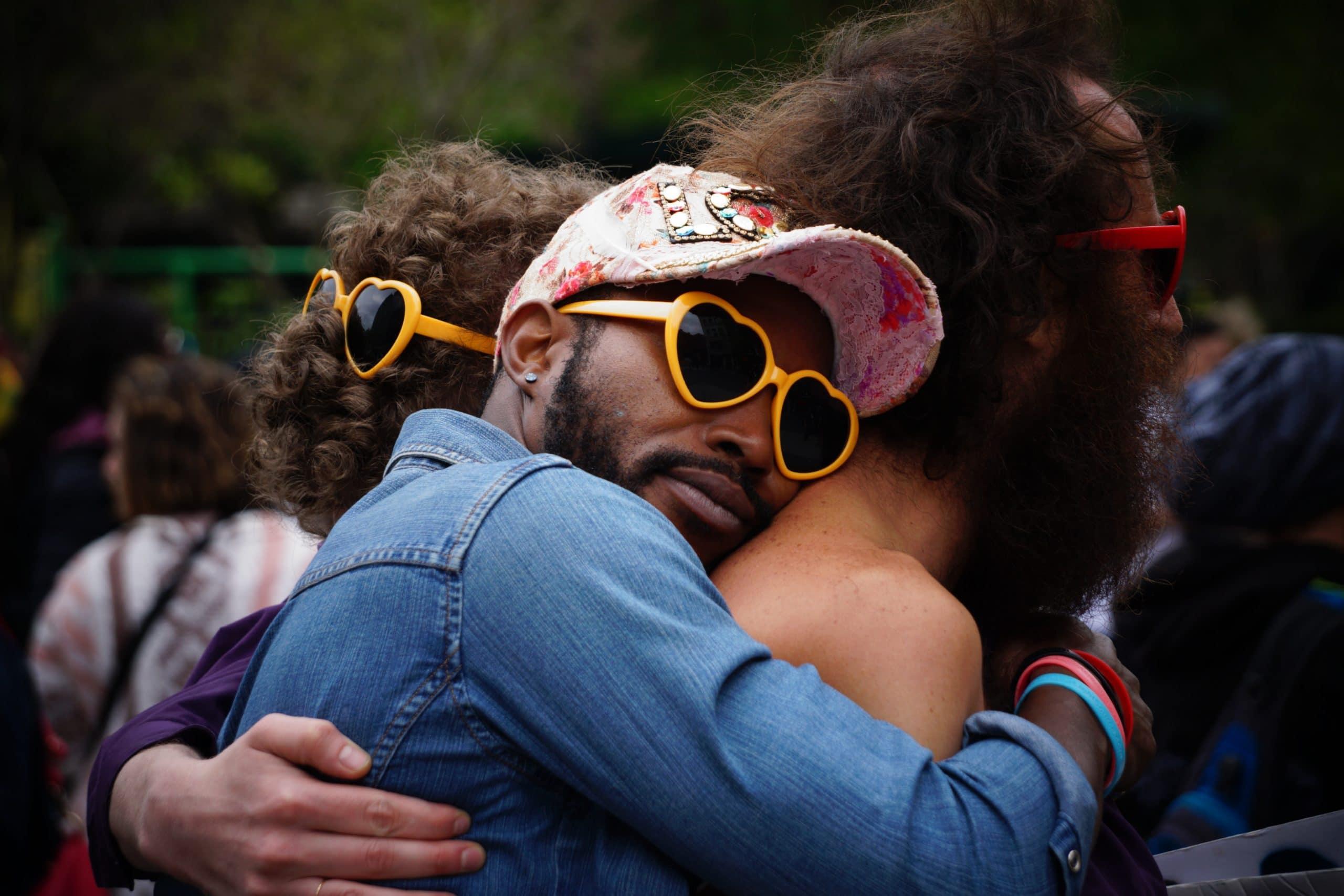 Três homens abraçados com óculos de sol.