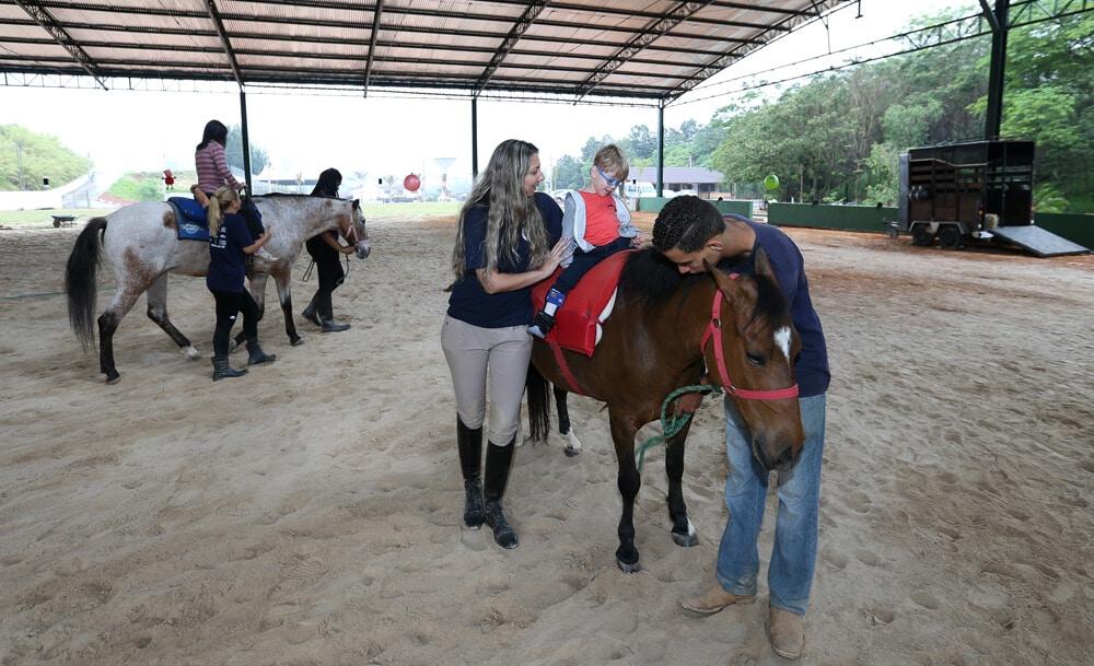 Equoterapeutas auxiliando menino a montar à cavalo.