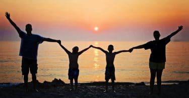Família de mãos dadas na praia.