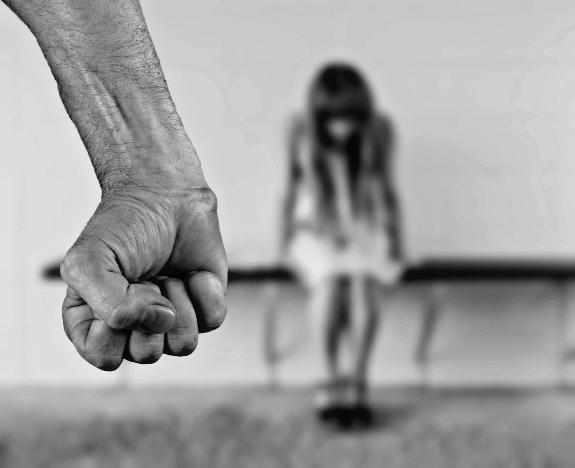 Punhos fechados de um homem com uma moça no fundo olhando para baixo.