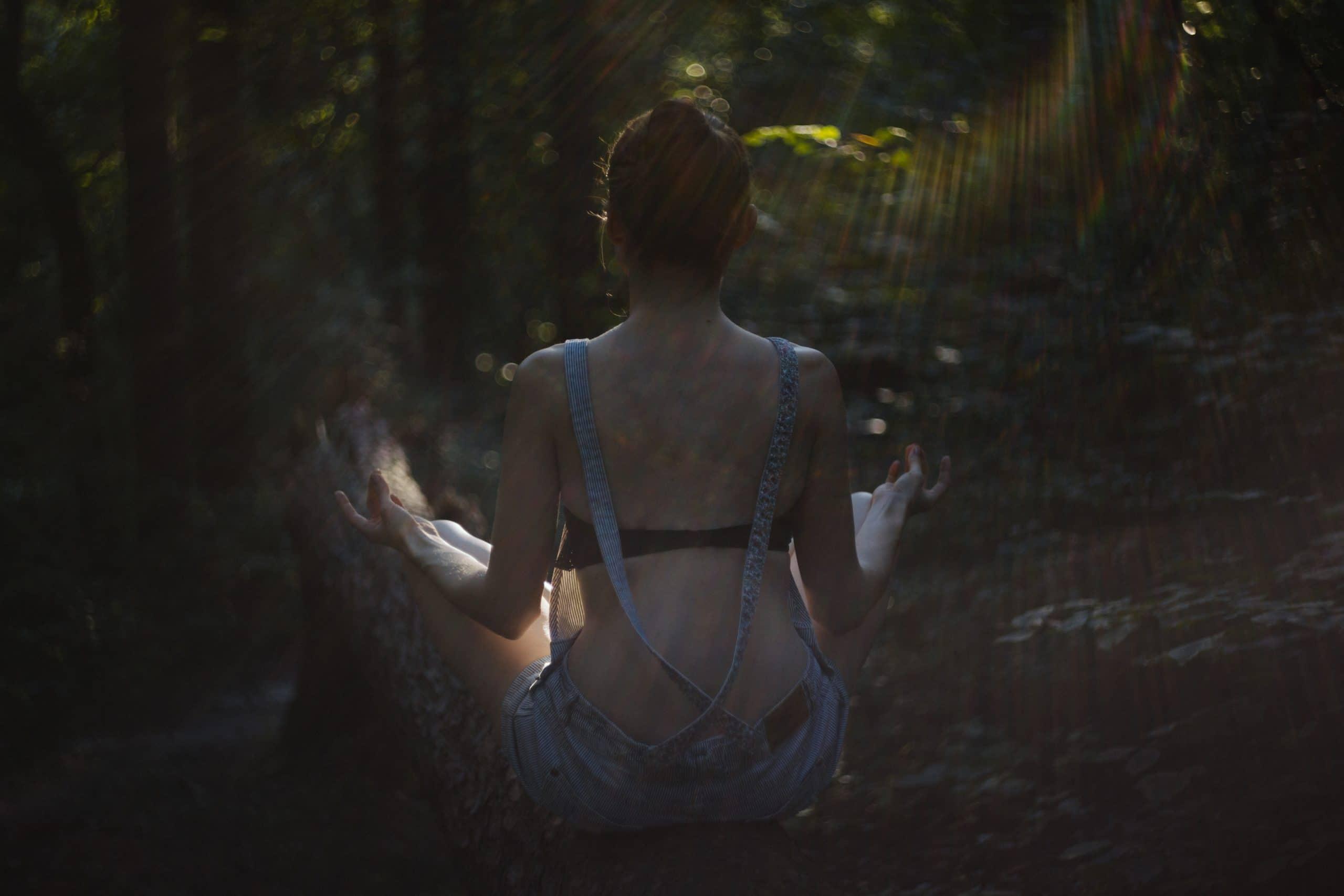 Mulher sentada de costas meditando