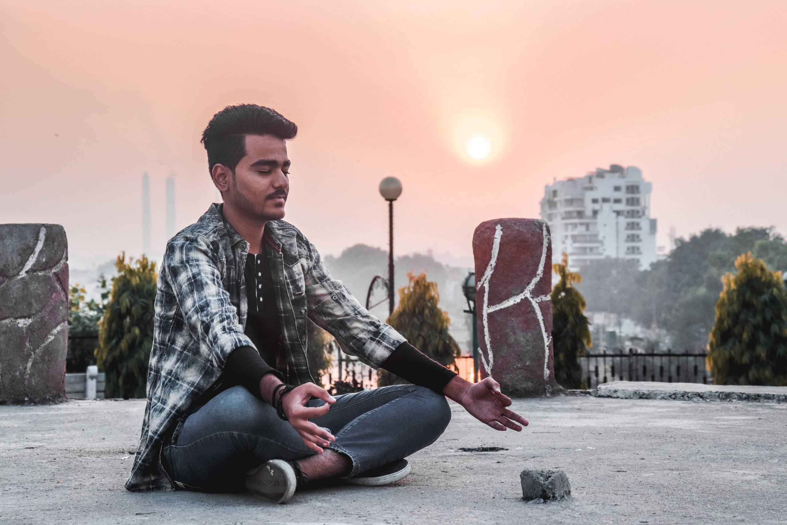 Homem meditando em cidade.