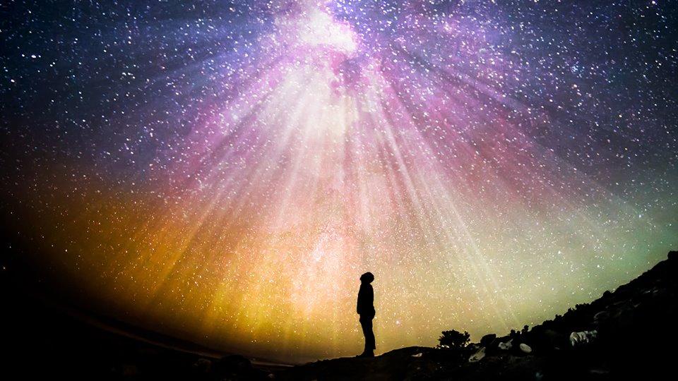 Homem olhando para céu estrelado.