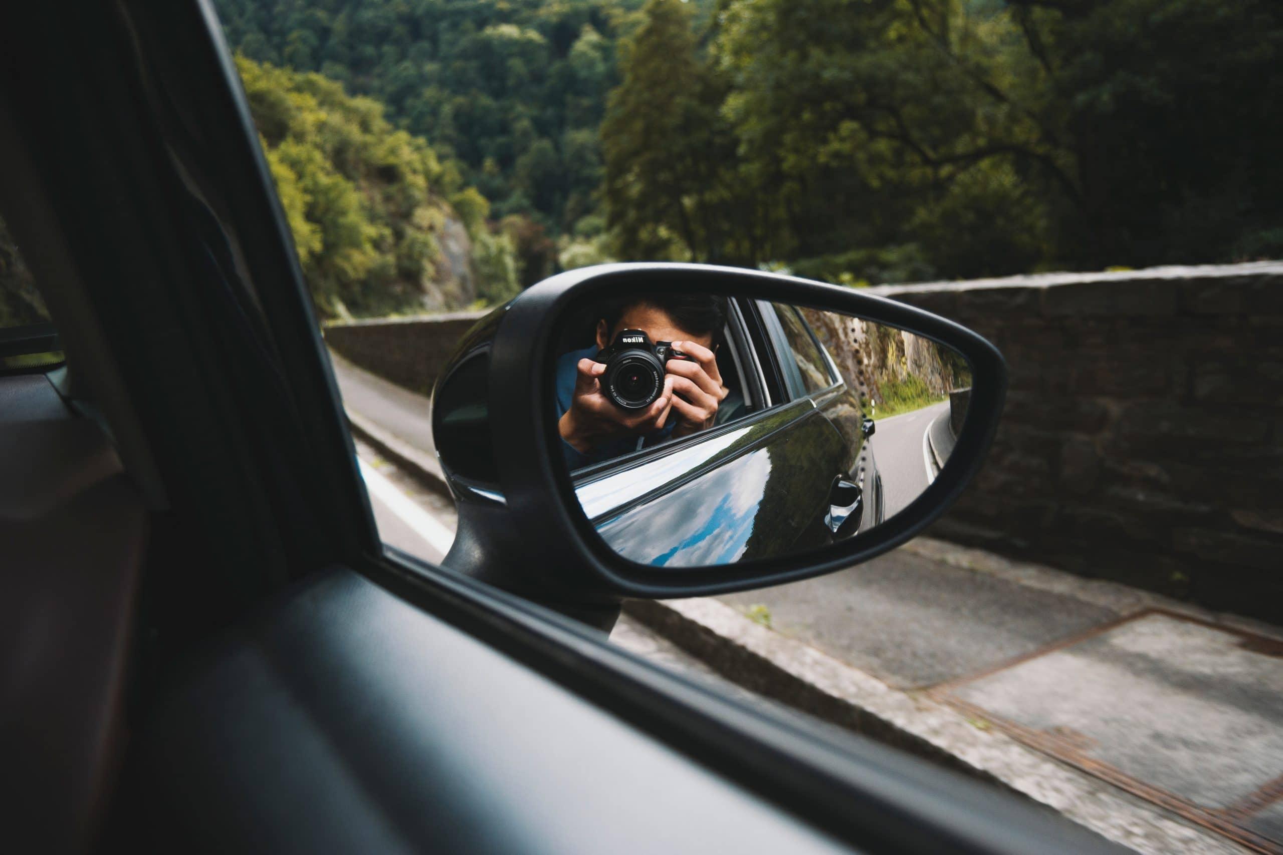 Homem tirando foto no retrovisor do carro.