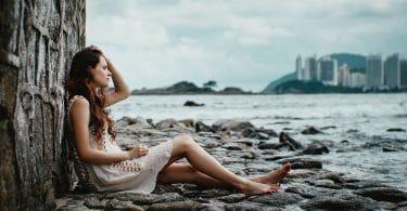 Mulher triste sentada em pedras