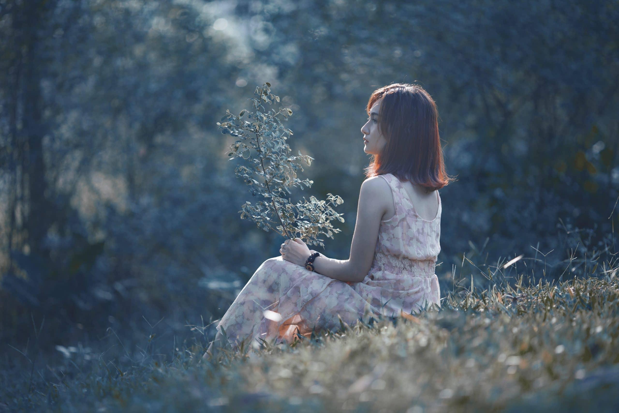Mulher sentada na grama segurando um ramo de plantas em suas mãos.