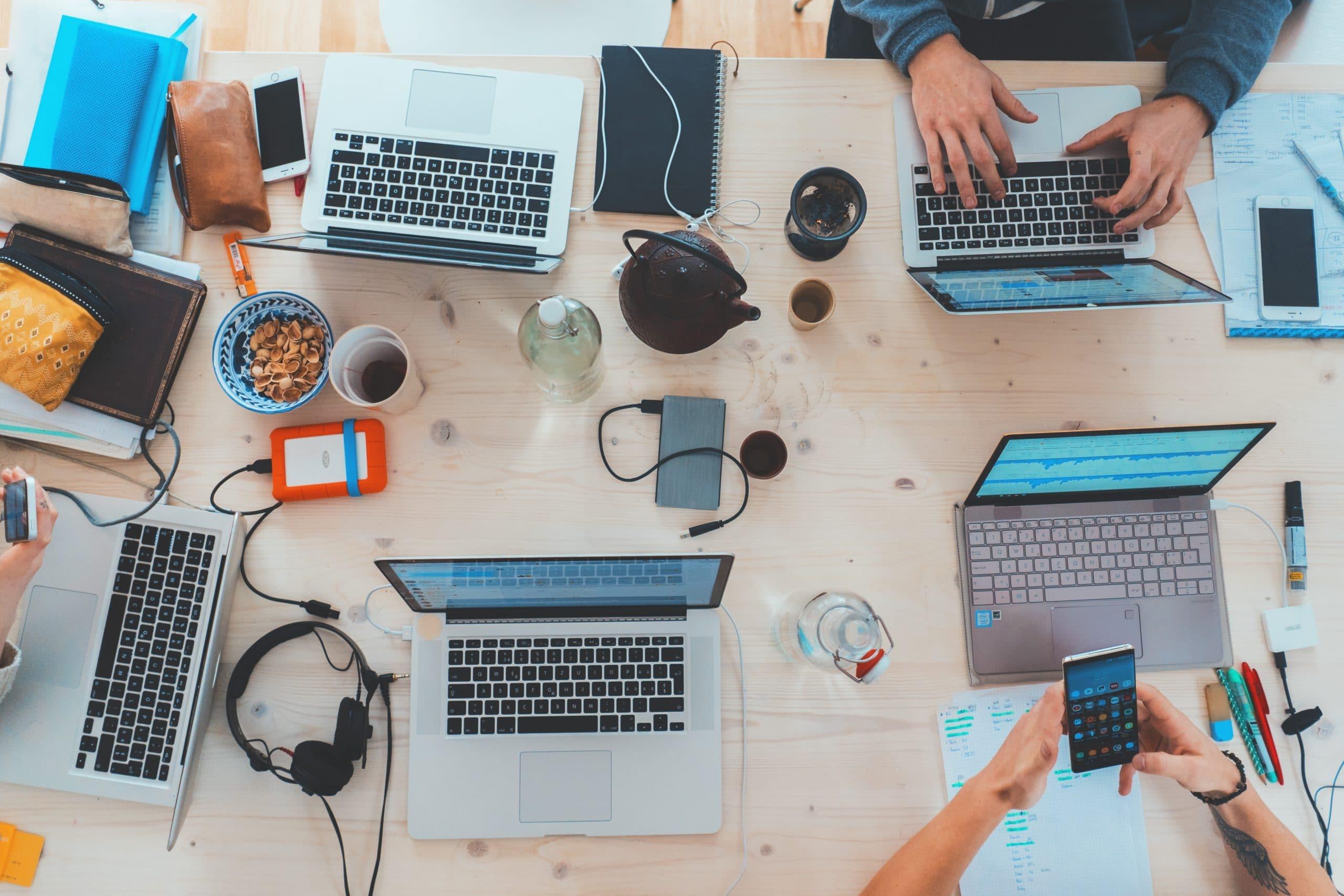 Mesa de trabalho com vários computadores.