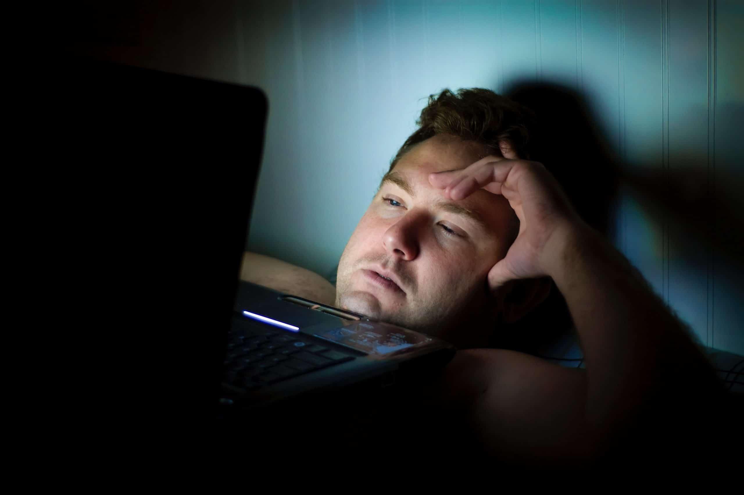 Homem exausto no computador durante a noite.