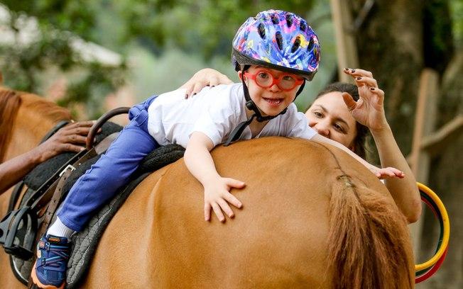 Menino sorrindo em cima de cavalo em equoterapia.