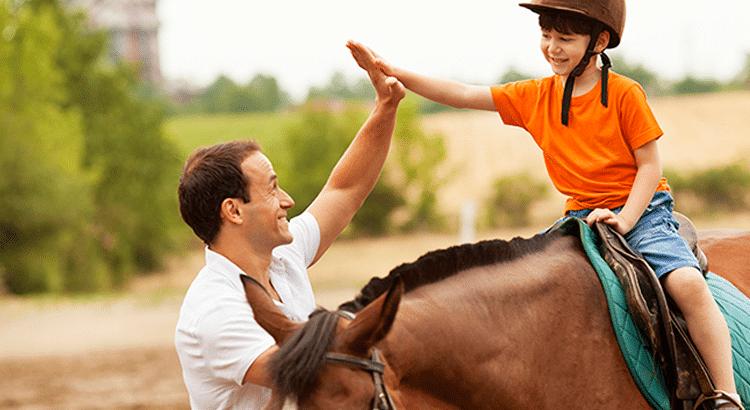 Menino sobre cavalo cumprimentando equoterapeuta.