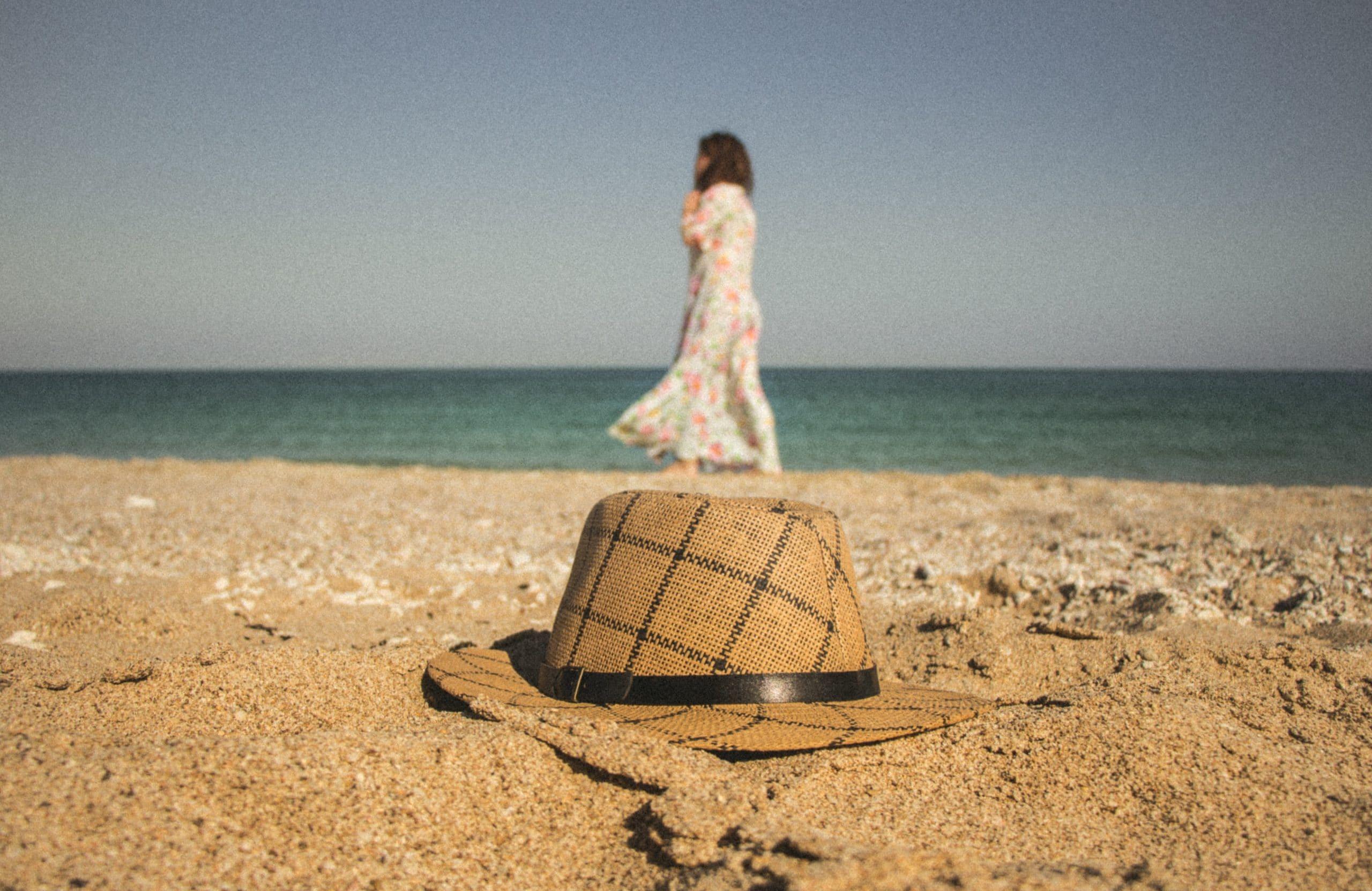Chapéu na areia da praia com mulher atrás.
