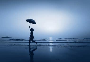 Mulher andando de guarda-chuva na praia à noite.