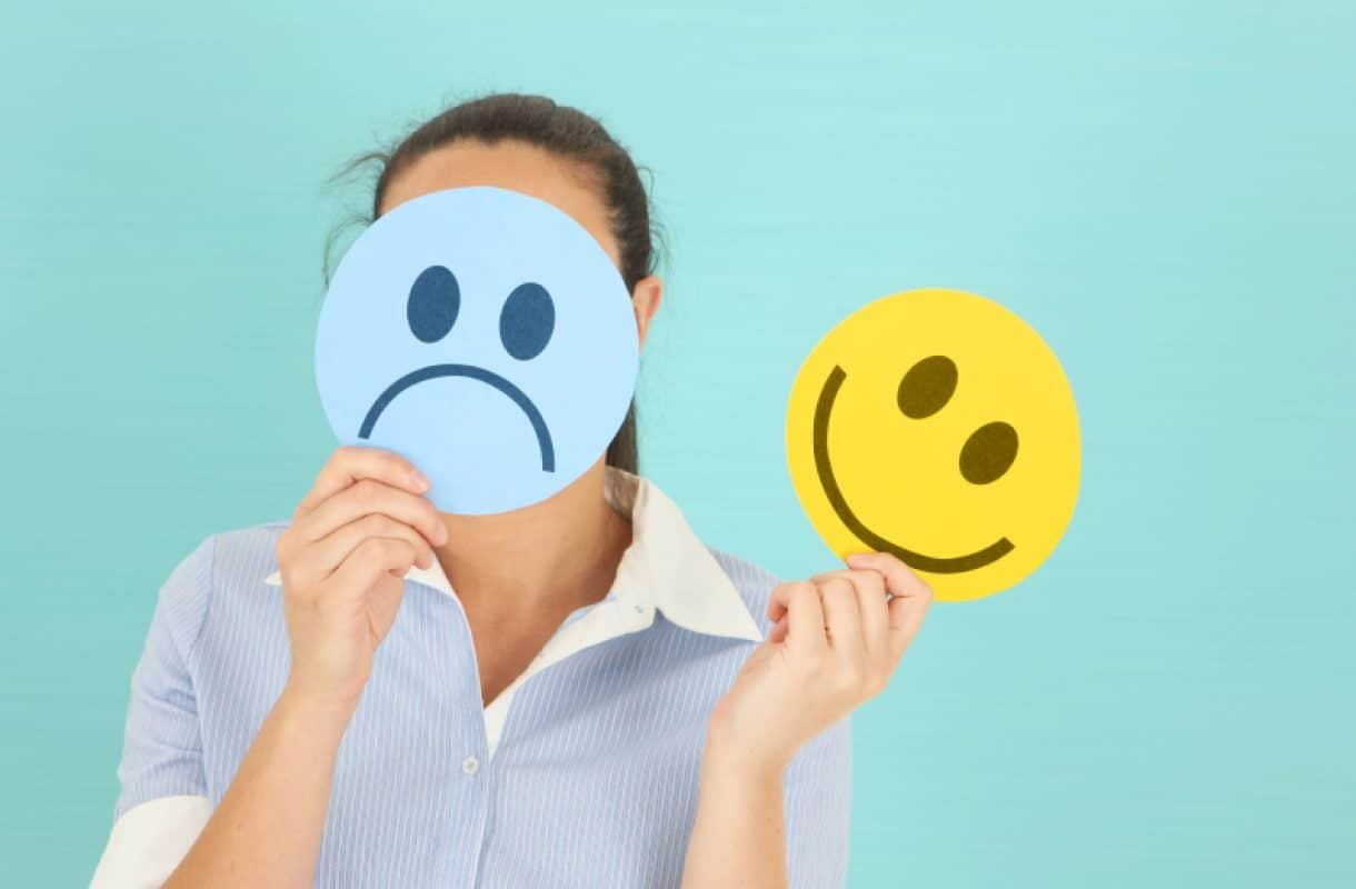 Mulher decidindo entre expressões triste e feliz.