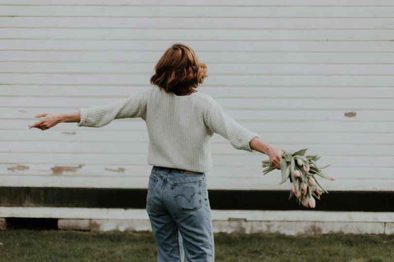 Mulher de costas com braços abertos segurando buquê de flores.