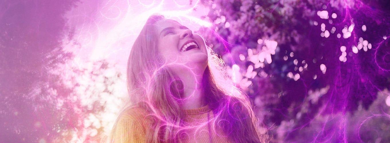 Mulher sorrindo sob desenhos de espirais rosas.