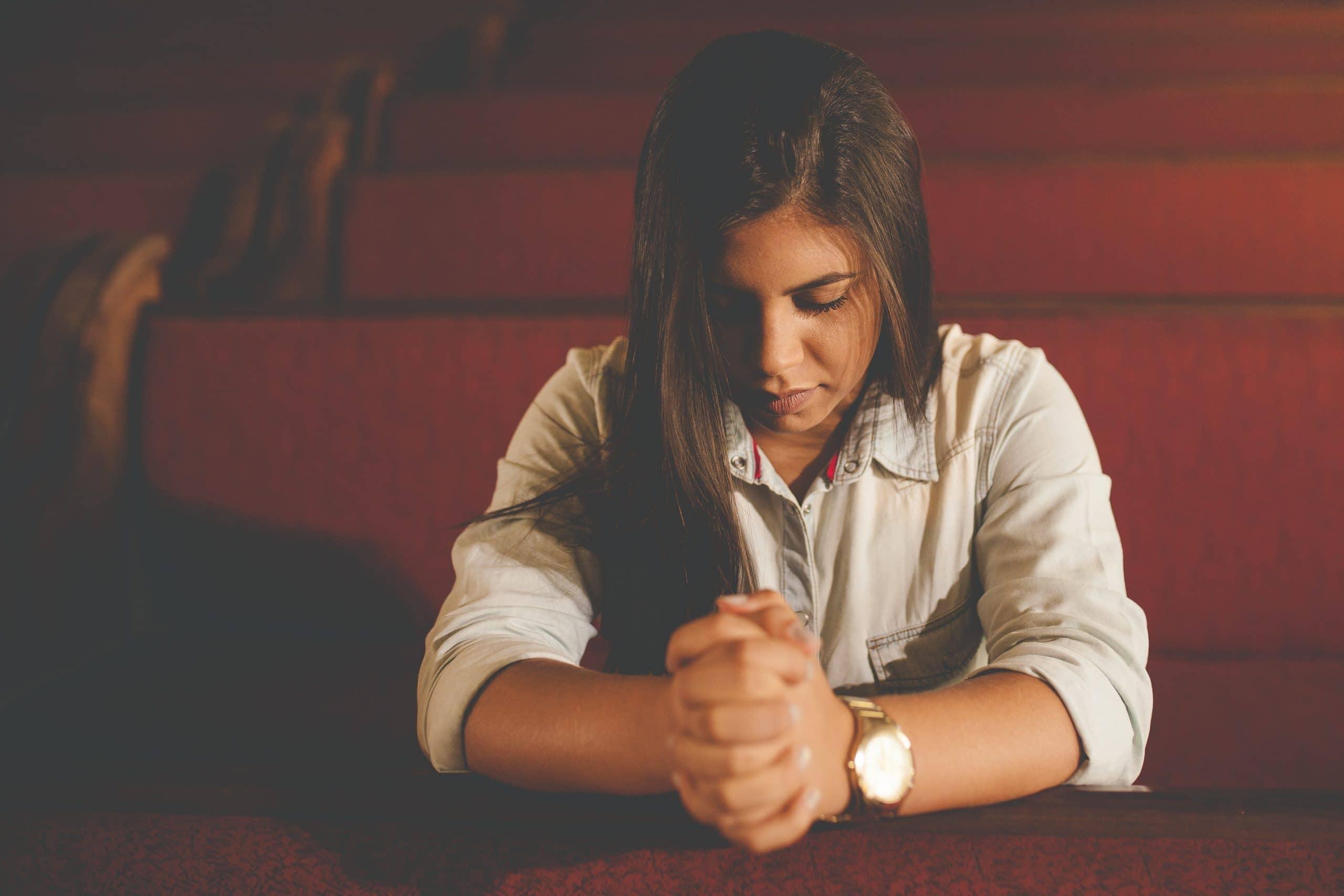 Mulher ajoelhada rezando