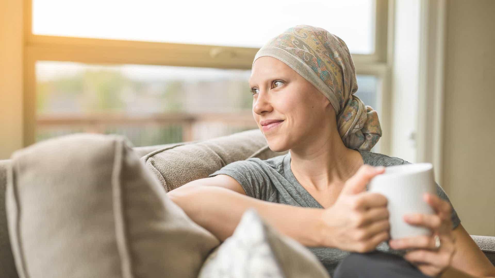 Mulher com câncer sorrindo com uma xícara na mão.