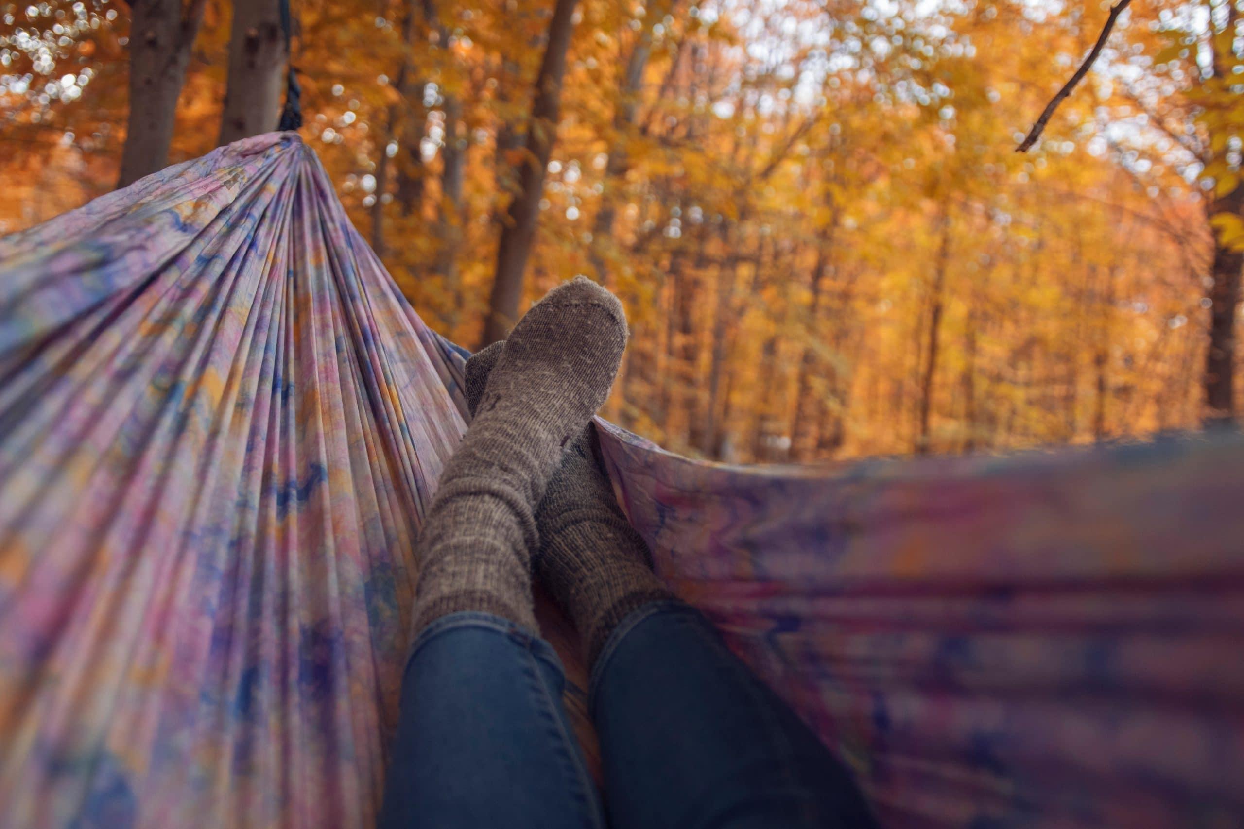 Pessoa relaxando na rede em floresta.