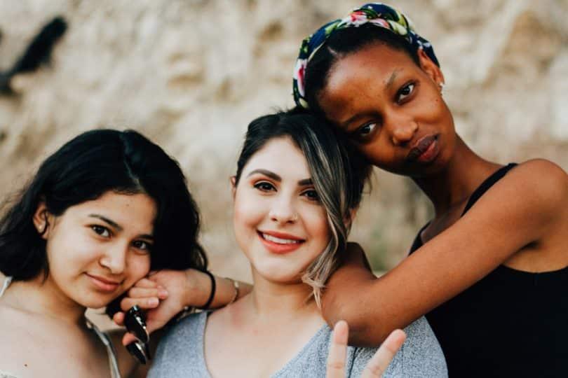 Três mulheres uma ao lado da outra sorrindo