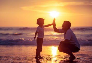 Pai e filho tocando as mãos em praia.