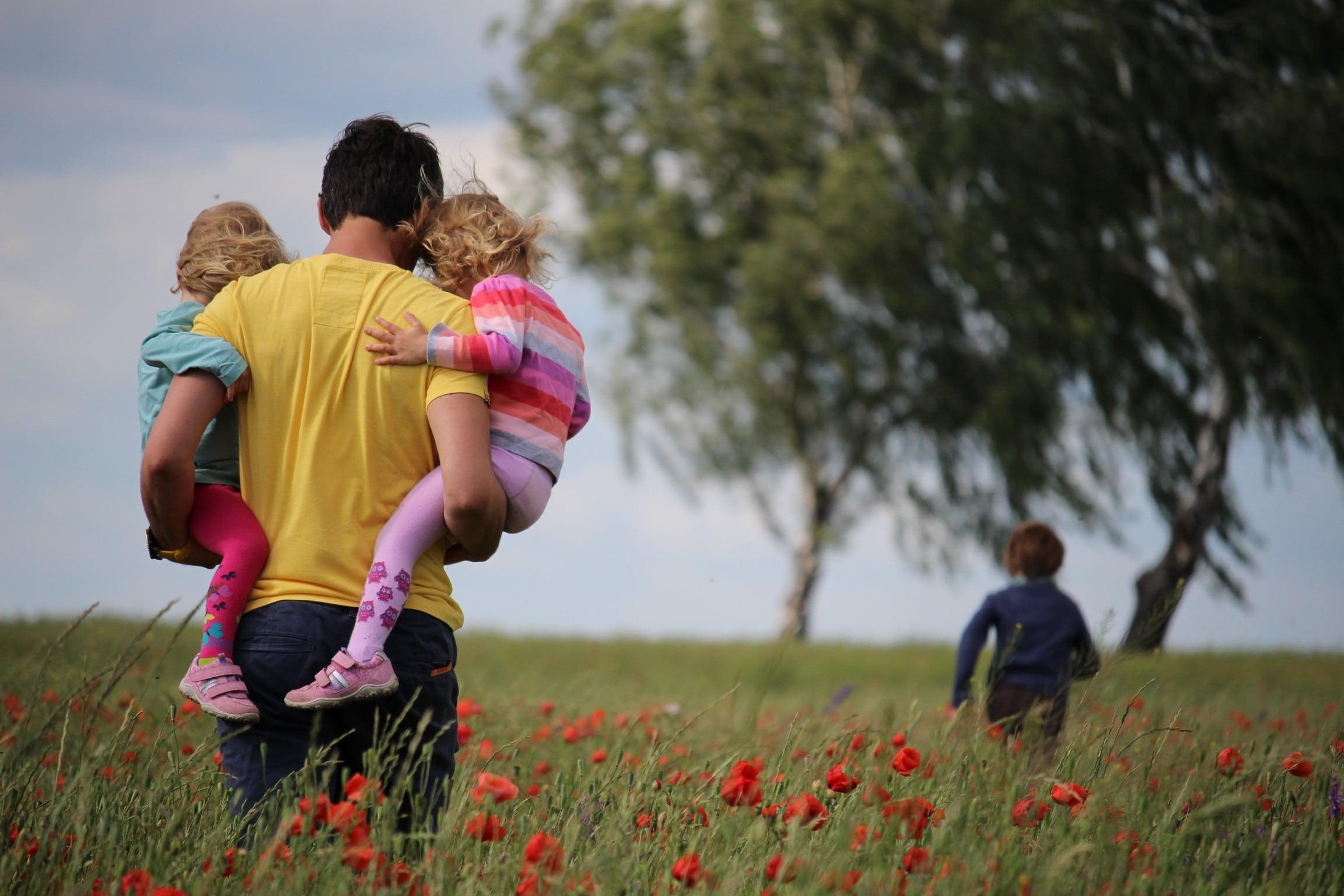 Pai levando crianças para passear no parque.