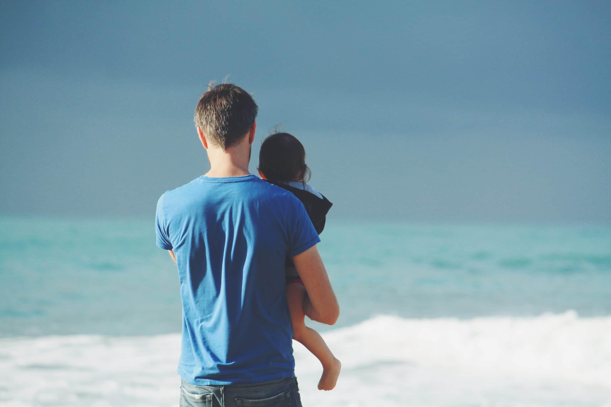 Pai segurando criança na praia.