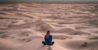 Mulher sentada de costas em deserto de areia