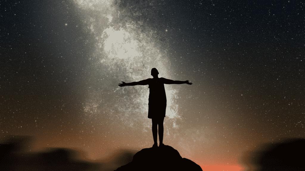 Silhueta de homem de braços abertos observando céu estrelado.