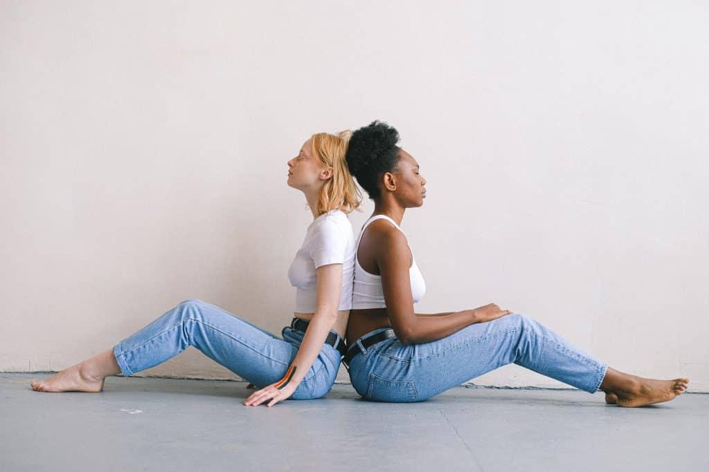 Duas mulheres sentadas no chão de costas uma para a outra