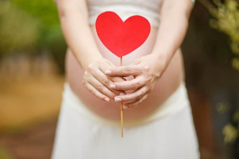 Mulher grávida segurando um palito com um coração grudado.