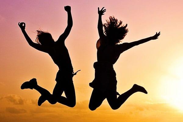 Duas pessoas pulando em dia ensolarado.