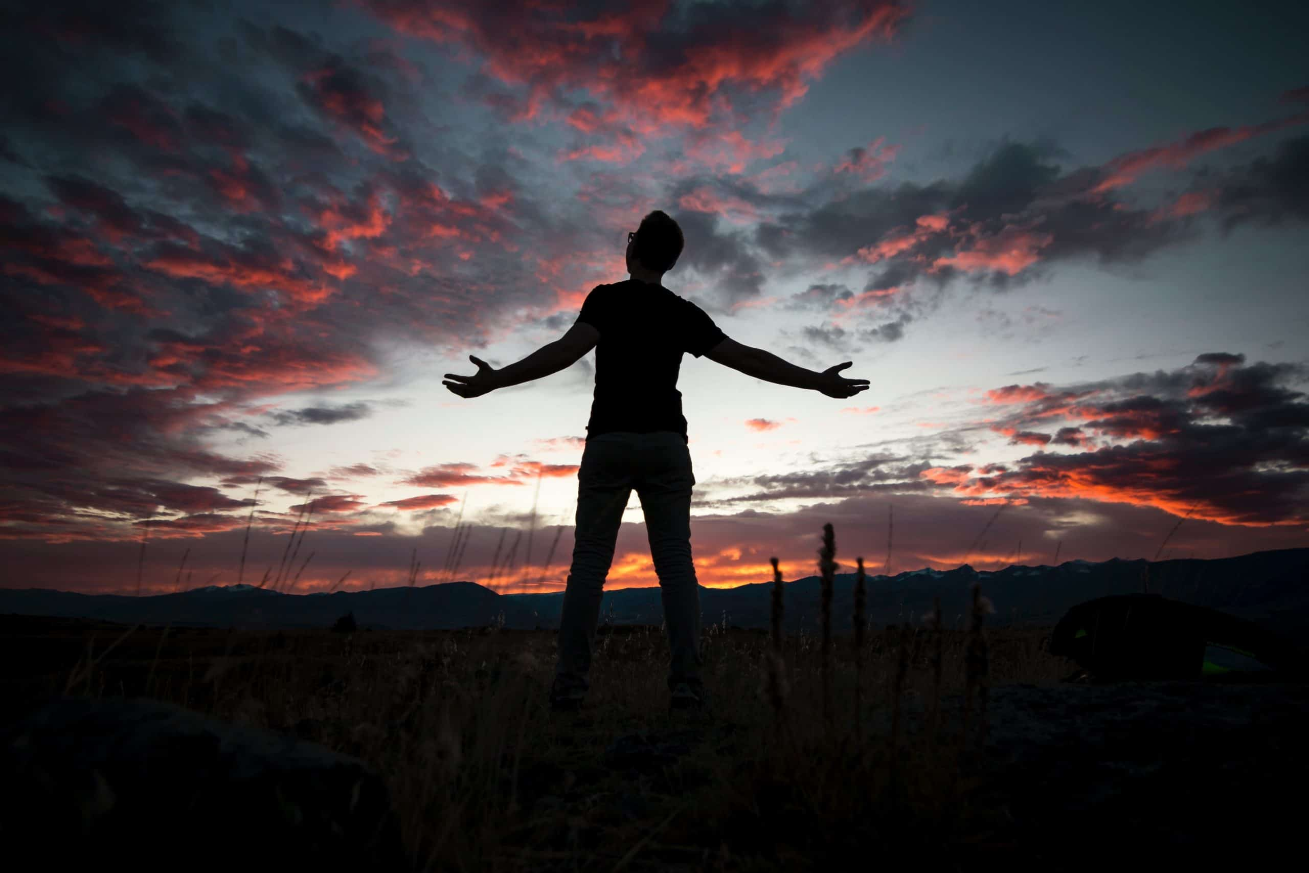 Homem com braços abertos durante o pôr-do-sol.