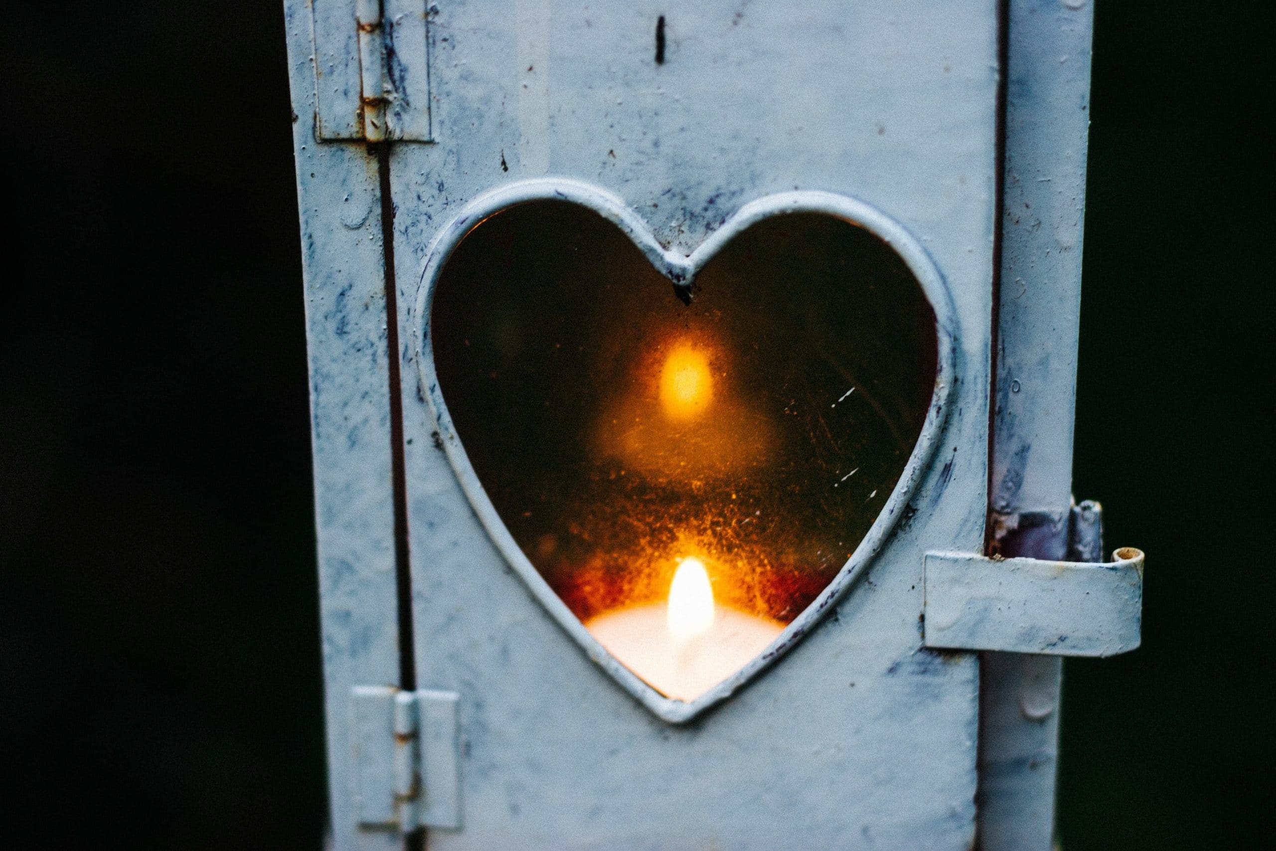 Vela acesa dentro de janela de coração.