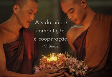 """Foto de dois monges ascendendo uma luz, com a frase """"A vida não é competição, é cooperação """" escrita em branco."""