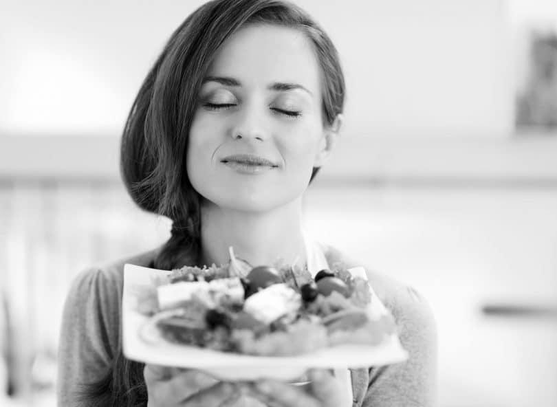 Foto preta e branca de mulher sorridente, de olhos fechados, segurando um prato de salada.