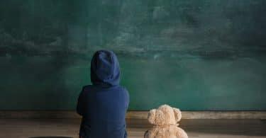 Criança sentada no chão, de costas, usando um moletom azul escuro, olhando para uma lousa. Ao seu lado, no chão, há um ursinho de pelúcia.