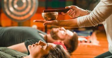 terapias integrativas : homem e mulher deitados no chão de madeira, com as cabeças apoiadas em travesseiros vermelhos. Em cima da cabeça da mulher, uma pessoa segura uma tigela de aço e um pedaço de madeira.