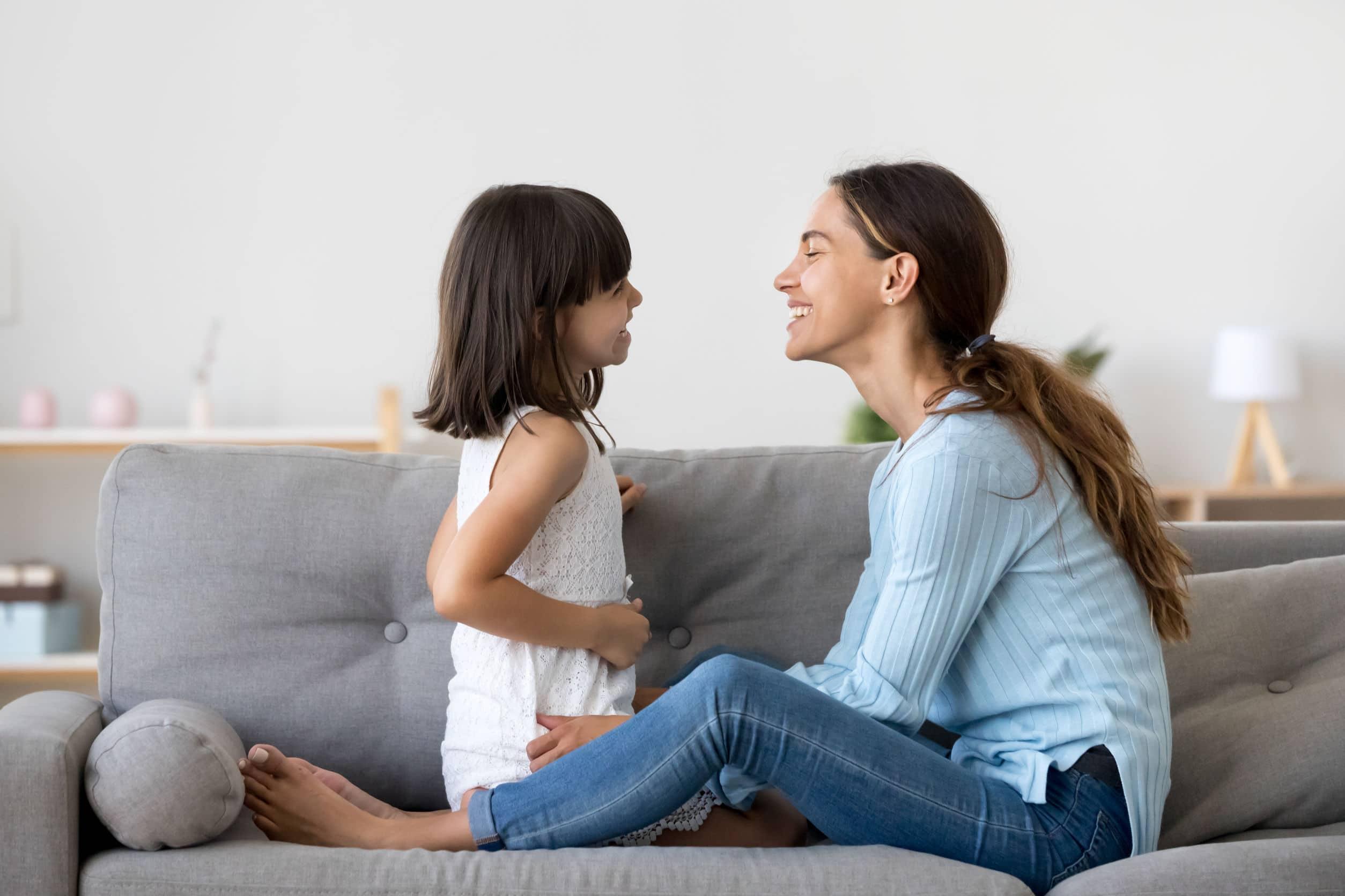 Mãe e filha olhando uma para a outra e sorrindo.