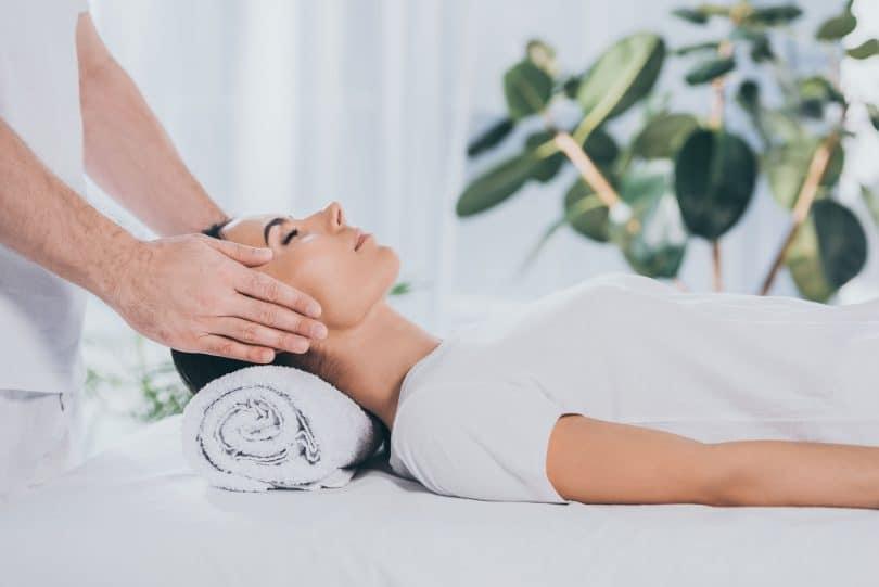 mulher jovem, calma, deitada em uma maca, com os olhos fechados, recebendo terapia de cura reiki