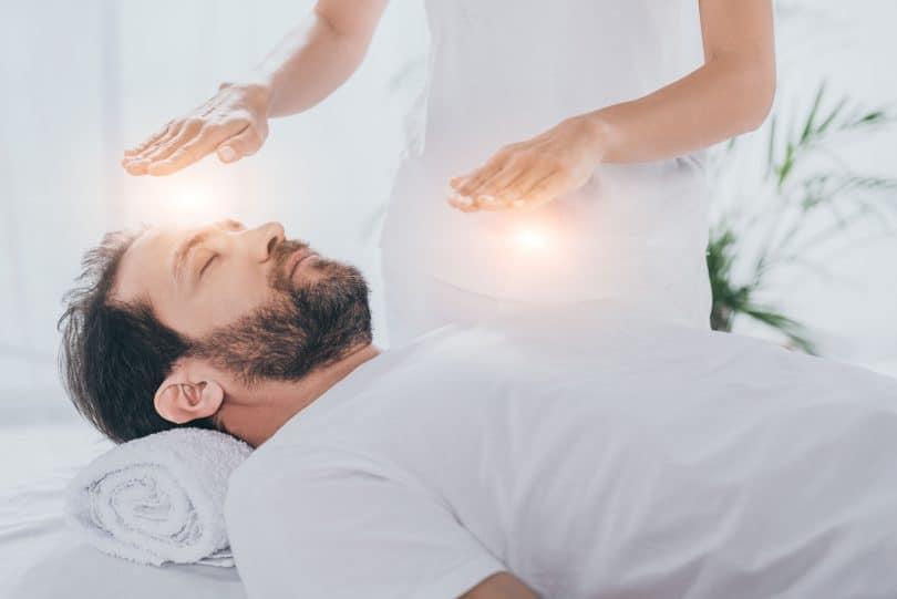Homem branco, jovem, barbudo, vestido de branco, deitado em uma maca, com uma outra pessoa em pé ao seu lado, colocando as mãos sobre ele, em uma sessão de reiki.